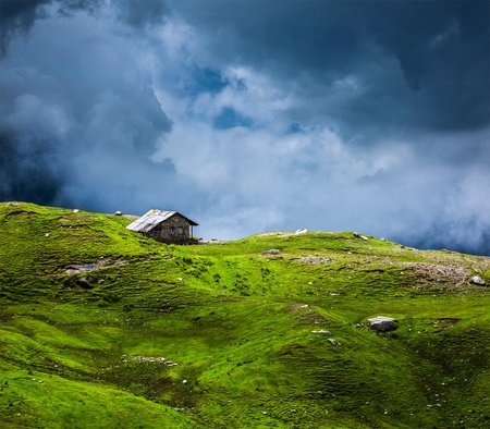 recluse: Serenity serene lonely scenery background concept - house in hills in mountins on alpine meadow in clouds