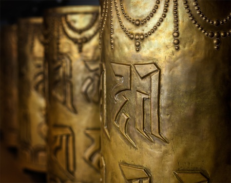 Tibetan Buddhist prayer wheels in Buddhism temple. Shallow depth of field. McLeod Ganj, HImachal Pradesh, India photo