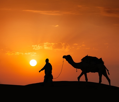 camel silhouette: camel driver with camel silhouette in dunes Stock Photo