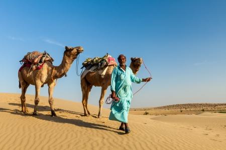 camello: camellero con camellos en las dunas del desierto de Thar Foto de archivo