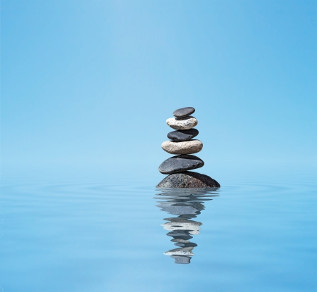 Zen meditation background -  balanced stones stack in water with reflection