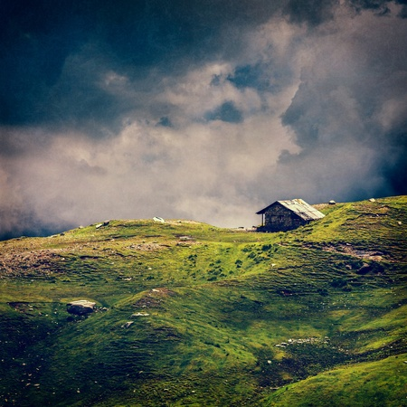 quiet scenery: Serenity serene lonely scenery background concept - old house in hills in mountins on alpine meadow in clouds. VIntage style cross process, grain and texture added