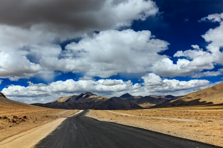 plains indian: Travel forward concept background - road on plains in Himalayas with mountains and dramatic clouds. Manali-Leh road, Ladakh, Jammu and Kashmir, India Stock Photo