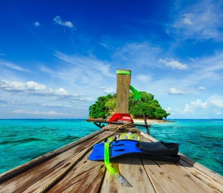 Vacation holidays adventure  concept background - tropical island and long-tail boat  with snorkeling set. Thailand photo