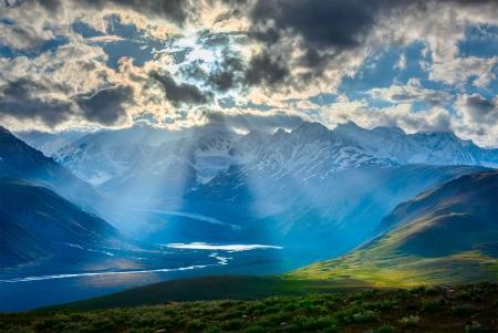 HImalayan valley landscape with Himalayas mountains. Sun rays come through clouds. Himachal Pradesh, India