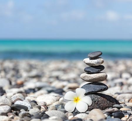 Zen meditatie spa ontspanning achtergrond - evenwichtige stenen stapelen met frangipani plumeria bloem close-up op zee strand