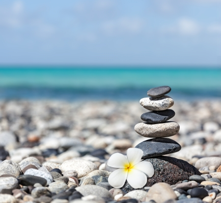 Zen meditation spa relaxation background -  balanced stones stack with frangipani plumeria flower close up on sea beach photo