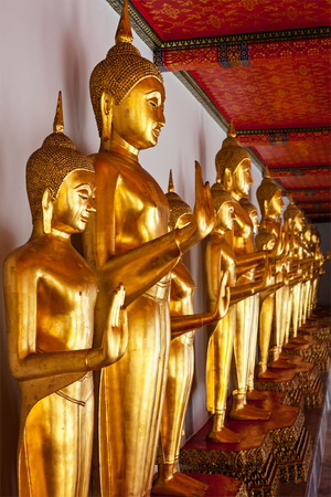 Standing golden Buddha statues close up. Wat Pho temple, Bangkok, Thailand photo