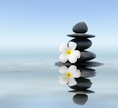 fengshui: Zen spa concept background - Zen massage stones with frangipani plumeria flower in water reflection