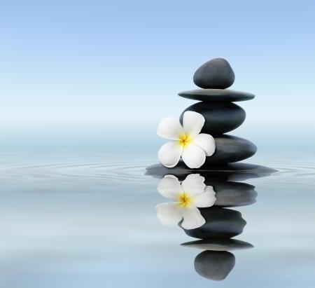 Zen spa concept background - Zen massage stones with frangipani plumeria flower in water reflection