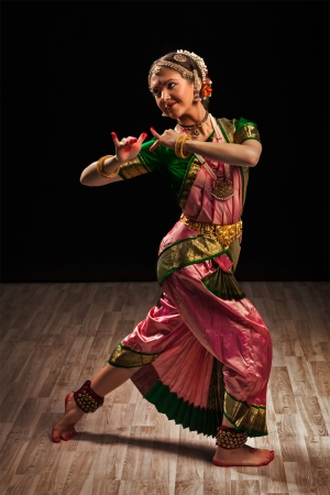 Young beautiful woman dancer exponent of Indian classical dance Bharatanatyam in Krishna pose photo