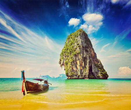 Retro vintage hipster style image of tropical vacation holiday beach concept - Long tail boat on tropical beach, Krabi, Thailand photo