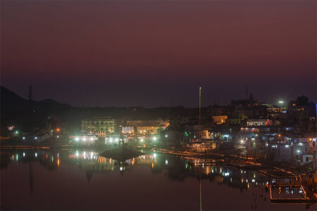 a bathing place: Sacred Puskhar lake (Sagar) and ghats of  town Pushkar in twilight in the evening, Rajasthan, India Stock Photo