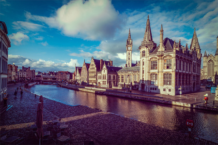 Vintage retro hipster style travel image of Ghent canal and Graslei street on sunset. Ghent, Belgium