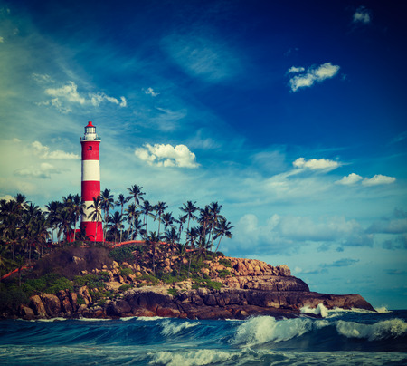 cross processed: Vintage retro hipster style travel image of old lighthouse and waves of  sea. Kovalam (Vizhinjam) Kerala, India