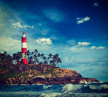kovalam: Vintage retro hipster style travel image of old lighthouse and waves of  sea. Kovalam (Vizhinjam) Kerala, India