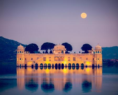 mughal architecture: Vintage retro hipster style travel image of Rajasthan landmark - Jal Mahal (Water Palace) on Man Sagar Lake in the evening in twilight.  Jaipur, Rajasthan, India