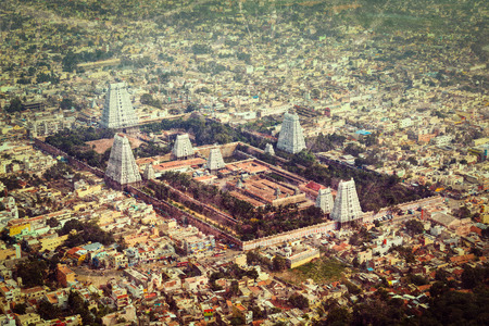 overpopulation: Vintage retro hipster style travel image of Hindu temple and indian city aerial view with grunge texture overlaid. Arulmigu Arunachaleswarar Temple, Tiruvannamalai, Tamil Nadu, India
