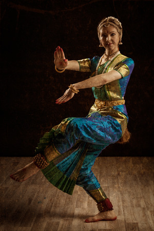 Vintage retro style image of young beautiful woman dancer exponent of Indian classical dance Bharatanatyam in Shiva pose photo