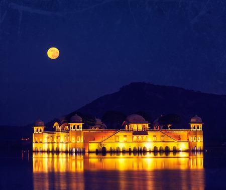 sagar: Vintage retro hipster style travel image of Rajasthan landmark - Jal Mahal (Water Palace) on Man Sagar Lake at night in twilight with grunge texture overlaid.  Jaipur, Rajasthan, India