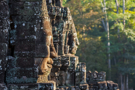thom: Ancient stone faces of Bayon temple, Angkor, Cambodia on sunset