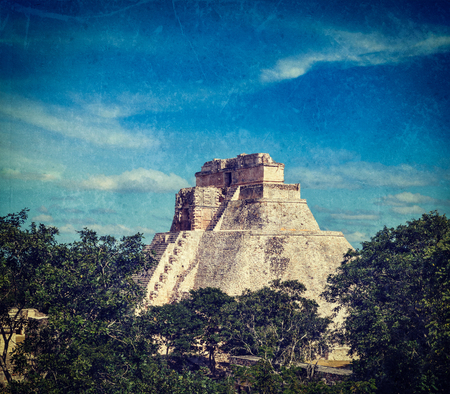 cross processed: Vintage retro hipster style travel image of anicent mayan pyramid (Pyramid of the Magician, Adivino) in Uxmal, Merida, Yucatán, Mexico with grunge texture overlaid Stock Photo