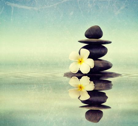 piedras zen: Imagen de la vendimia retro estilo inconformista viajes de Zen spa concepto de fondo - Zen piedras de masaje con flores plumeria frangipani en la reflexión del agua con el grunge textura superpuesta