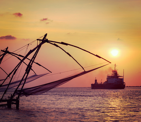 india fisherman: Vintage retro hipster style travel image of Kochi chinese fishnets on sunset and modern ship. Fort Kochin, Kochi, Kerala, India Stock Photo