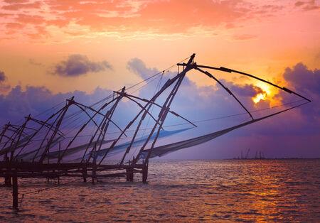 chinese fishing nets: Vintage retro hipster style travel image of Kochi chinese fishnets on sunset with grunge texture overlaid. Fort Kochin, Kochi, Kerala, India