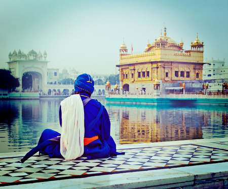 Vintage retro hipster style travel image of unidentifiable Seekh Nihang warrior meditating at Sikh temple Harmandir Sahib. Amritsar, India Editorial