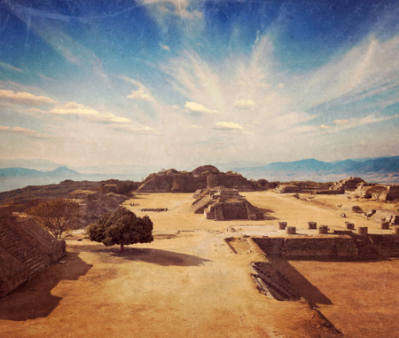 Vintage retro hipster style travel image of ancient civilization ruins on plateau Monte Alban in Mexico with grunge texture overlaid photo