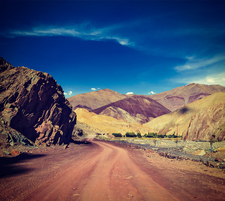cross processed: Vintage retro effect filtered hipster style travel image of Travel forward concept background - road Himalayas with mountains. Manali-Leh road, Ladakh, Jammu and Kashmir, India