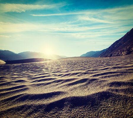cross processed: Vintage retro effect filtered hipster style travel image of Sand dunes in Himalayas on sunrise. Hunder, Nubra valley, Ladakh, India