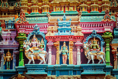 parvati: Vintage retro hipster style travel image of Shiva and Parvati on bull images. Sculptures on Hindu temple gopura (tower). Menakshi Temple, Madurai, Tamil Nadu, India Stock Photo