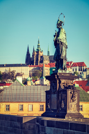 martyr: Vintage retro hipster style travel image of John of Nepomuk (or John Nepomucene) national saint of the Czech Republic statue on Charles Brigde at the site where the saint was thrown into Vltava with St. Vitus Cathedral in background in Prague Stock Photo