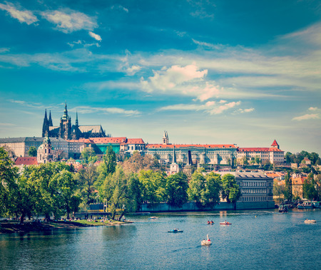 prague: Vintage retro hipster style travel image of panorama view of Vltava river and Gradchany (Prague Castle) and St. Vitus Cathedral and Charles bridge an people in paddle boats in the Prague, Czech Republic