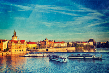 Vintage retro hipster style travel image of Vltava river with tourist boats and Prague Stare Mesto embankment view from Charles bridge on sunset with grunge texture overlaid. Prague, Czech Republic