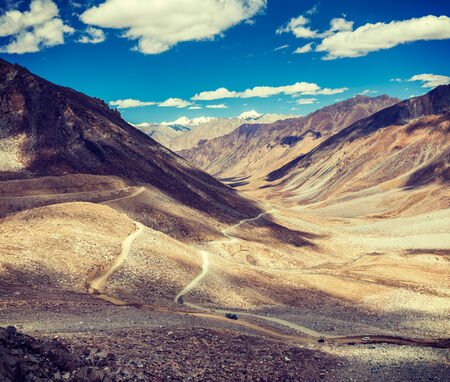 unsurfaced road: Vintage retro effect filtered hipster style travel image of Himalayan valley landscape with road near Kunzum La pass - allegedly the highest motorable pass in the world (5602 m), Ladakh, India