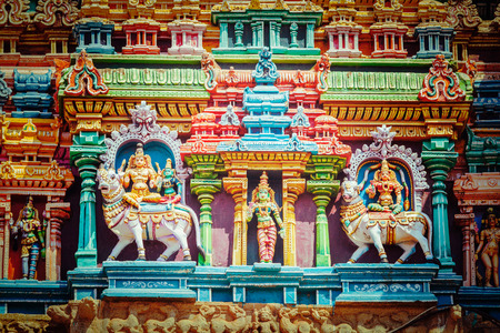 temple tower: Vintage retro hipster style travel image of Shiva and Parvati on bull images. Sculptures on Hindu temple gopura (tower). Menakshi Temple, Madurai, Tamil Nadu, India Stock Photo