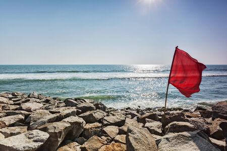 forbidding: Danger - Red flag on rocky beach forbidding to swim Stock Photo