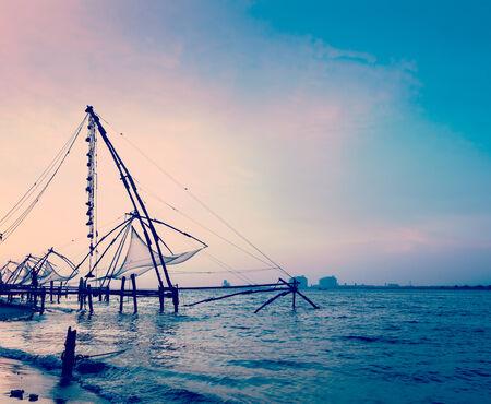 india fisherman: Vintage retro hipster style travel image of Kochi chinese fishnets on sunset. Fort Kochin, Kochi, Kerala, India