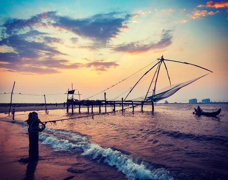 Vintage retro hipster style travel image of Kochi chinese fishnets on sunset. Fort Kochin, Kochi, Kerala, India photo
