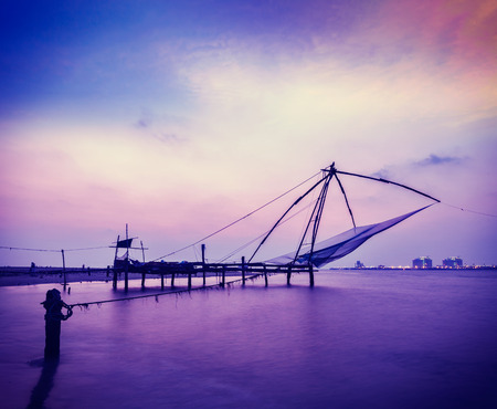 kochi: Vintage retro hipster style travel image of Kochi chinese fishnets on sunset. Fort Kochin, Kochi, Kerala, India