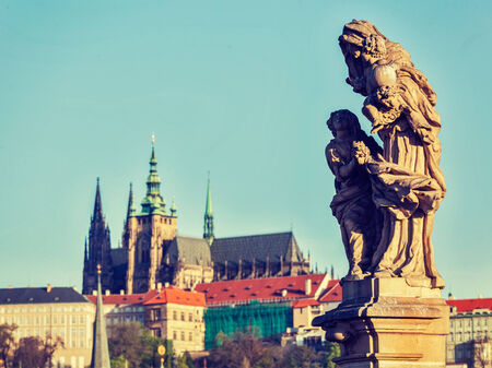 czechoslovakia: Vintage retro hipster style travel image of statue on Charles Brigde with St. Vitus Cathedral in background in Prague
