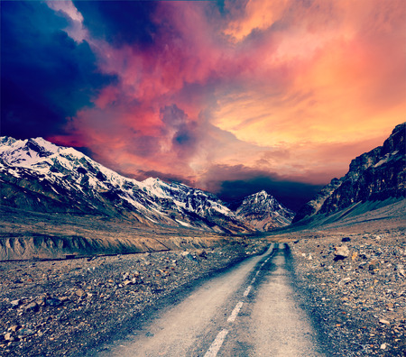 unsurfaced road: Vintage retro effect filtered hipster style travel image of road in mountains Stock Photo