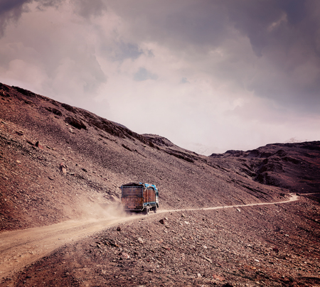unsurfaced road: Vintage retro effect filtered hipster style travel image of Manali-Leh Road in Indian Himalayas with lorry. Himachal Pradesh, India Stock Photo