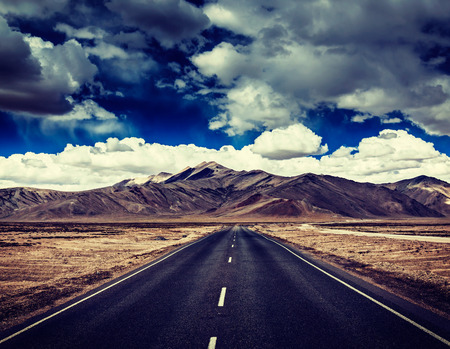plains indian: Vintage retro effect filtered hipster style travel image of Travel forward concept background - road on plains in Himalayas with mountains and dramatic clouds. Manali-Leh road, Ladakh, Jammu and Kashmir, India