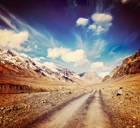 unsurfaced road: Vintage retro effect filtered hipster style travel image of Road in mountains (Himalayas). Spiti Valley,  Himachal Pradesh, India Stock Photo