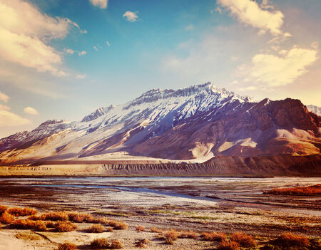 horizontals: Vintage retro effect filtered hipster style travel image of Spiti Valley -  snowcapped Himalayan Mountains. Himachal Pradesh, India Stock Photo