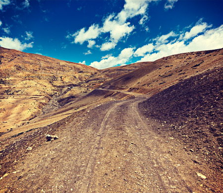 unsurfaced road: Vintage retro effect filtered hipster style travel image of dirt road in mountains (Himalayas). Spiti Valley,  Himachal Pradesh, India Stock Photo